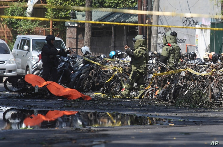 Members of a police bomb squad inspect the wreckage of motorcycles where an explosion went off outside a church in Surabaya, East Java, Indonesia, May 13, 2018.