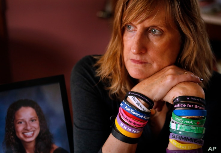 FILE - Judi Richardson, a citizen sponsor of a ballot initiative to require background checks for gun buyers, wears wrist bands bearing the names and places of victims of gun violence, at her home in South Portland, Maine.