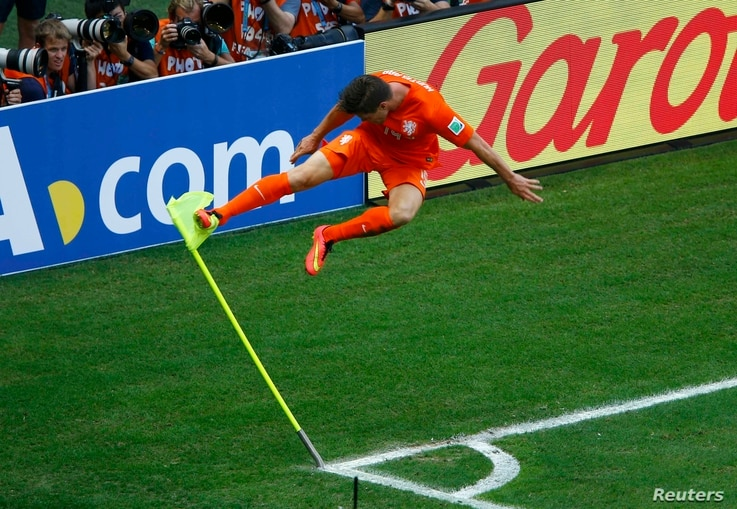 Klaas-Jan Huntelaar of the Netherlands kicks a corner flag to celebrate his goal against Mexico at the Castelao arena in Fortaleza, June 29, 2014.