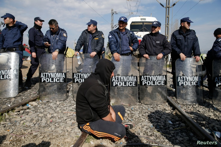 A migrant sits next to the riot police as other migrants block the railway track at the Greek-Macedonian border, near the village of Idomeni, Greece, March 3, 2016.