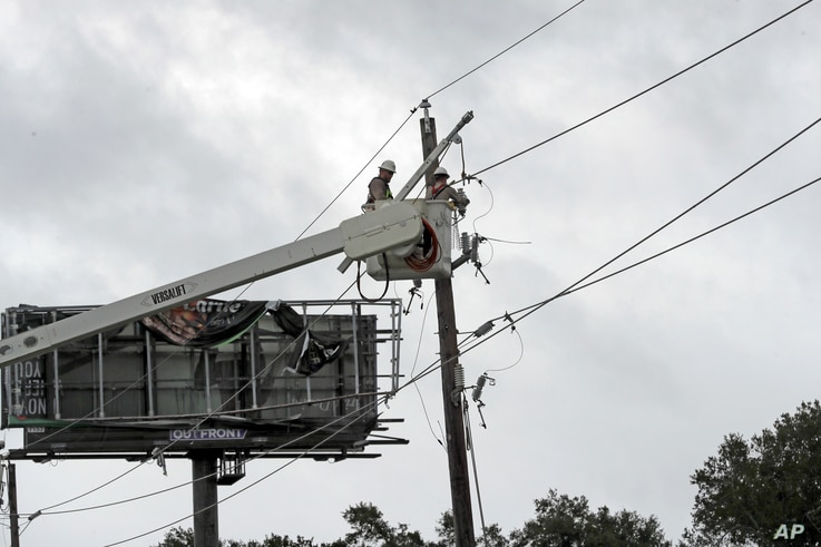 Power company workers repair damaged power lines damages from Hurricane Harvey, in Katy, Texas, Aug. 26, 2017.