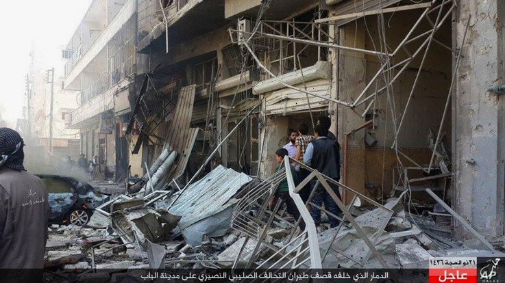 In this Oct. 5, 2015 photo released by the Rased News Network, a Facebook account affiliated with Islamic State militants, which has been authenticated based on its contents and other AP reporting, people gather at the site of an airstrike in Al-Bab