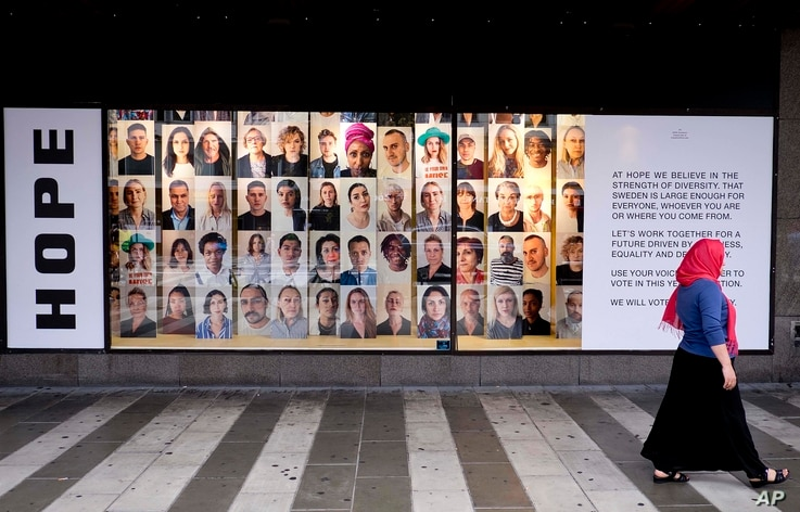 A woman walks by an advertising for diversity and tolerance in the window of shopping mall in Stockholm, Sweden, Aug. 31, 2018.