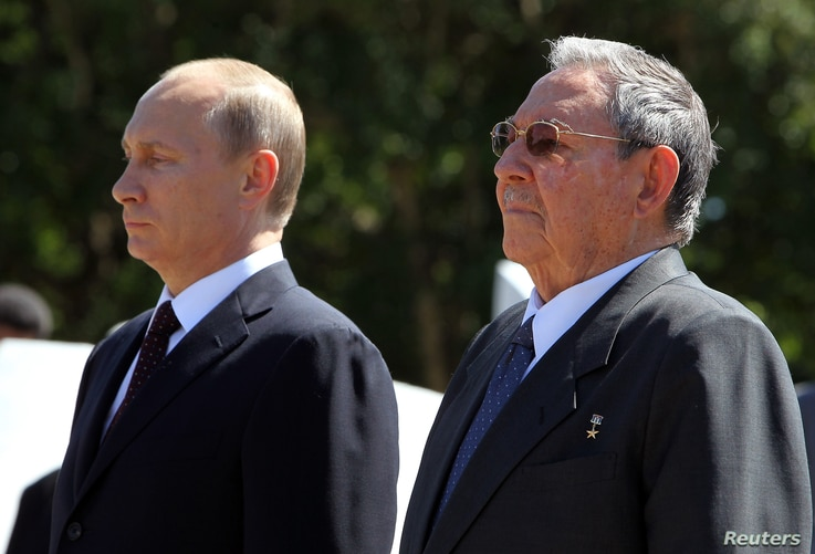 Russian President Vladimir Putin (L) stands next to Cuba's President Raul Castro as they attend a wreath-laying ceremony at the Soviet Soldier monument in Havana, July 11, 2014.