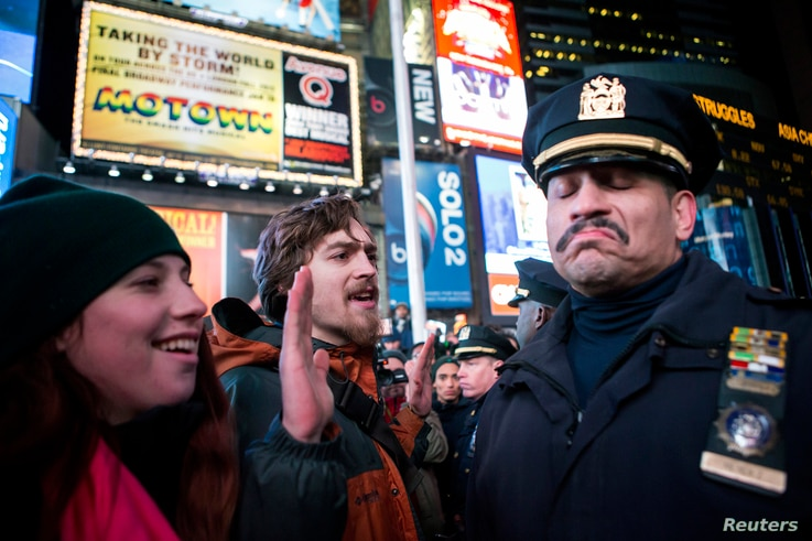 A NYPD policeman (R) reacts next to people protesting against the Staten Island death of Eric Garner during an arrest in July, at midtown Manhattan in New York December 3, 2014. A New York City grand jury decision not to charge white police officer D...
