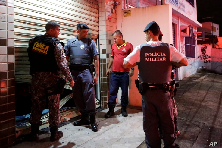 Military police check the broken entrance of a store that was looted in Vitoria, Espirito Santo state, Brazil, Feb 8, 2017.