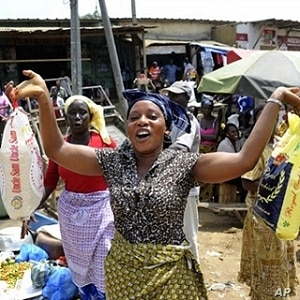 A woman holds bags of rice at a market in Abidjan.  Some economists say food scarcity and rising prices could lead to social instability.