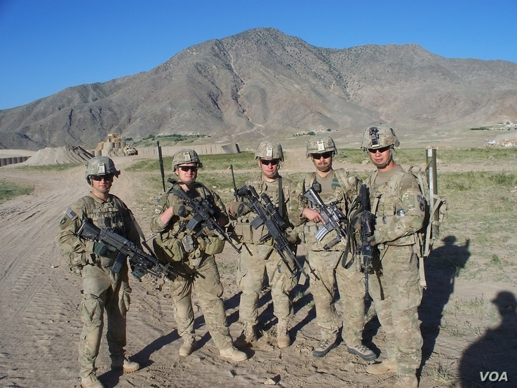 Sergeant Clayton Embre, far right, and Sergeant Devin Burgett, second from right, pose with comrades.
