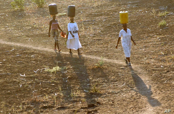 FILE - Women carry water for domestic use from the Limpopo river to their homes in the Salani Village, Mozambique, September 2005.
