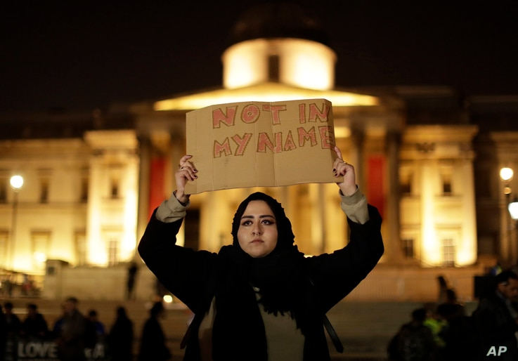 A woman holds up a sign at a vigil for the victims of Wednesday's attack, at Trafalgar Square in London, March 23, 2017. The Islamic State group has claimed responsibility for an attack by a man who plowed an SUV into pedestrians and then stabbed a p