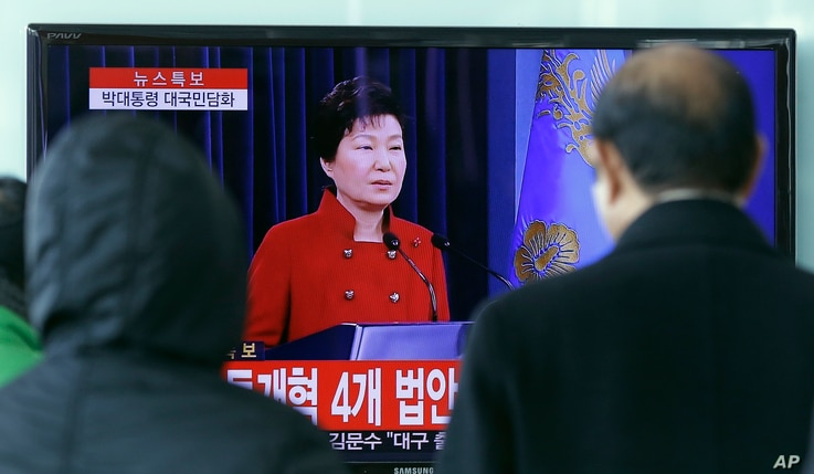 FILE - People watch a live broadcast of South Korean President Park Geun-hye's press conference, at the Seoul Railway Station in Seoul, South Korea, Jan. 13, 2016. Park called for resumption of nuclear talks, even if Pyongyang does not participate.  ...