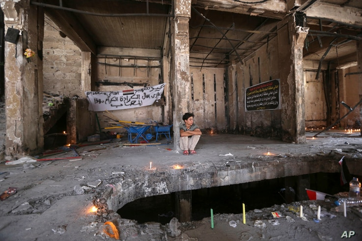 A man sits amid a makeshift memorial inside a burned mall at the scene of a massive truck bombing last Sunday that killed at least 186 people and was claimed by the Islamic State group, in the Karada neighborhood of Baghdad, Iraq, July 10, 2016.