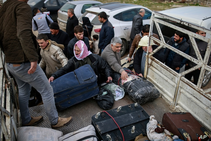 Syrians put their belongings into vehicles after crossing into Turkey at the Cilvegozu border gate with Syria, near Hatay, southeastern Turkey, Dec. 18, 2016.