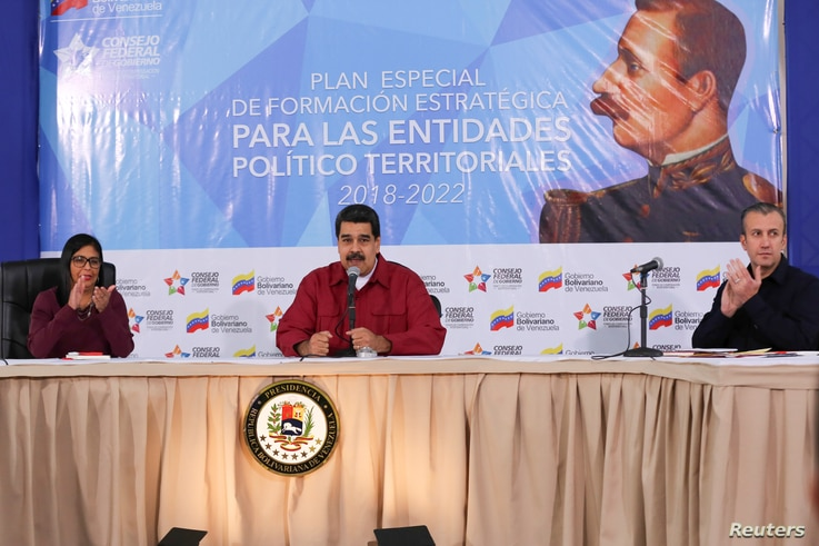 Venezuela's President Nicolas Maduro (C) speaks during a meeting with pro-government governors and mayors, next to Venezuela's National Constitutional Assembly Delcy Rodriguez (L) and Venezuela's Vice President Tareck El Aissami, at Miraflores Palace