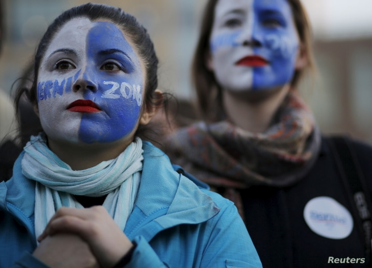 FILE - Natalia Plaza, left, and Suzanne Tufan, with their faces painted, wait for a campaign rally with U.S. Democratic presidential candidate Bernie Sanders in Washington Square Park in the Greenwich Village neighborhood of New York, April 13, 2016....