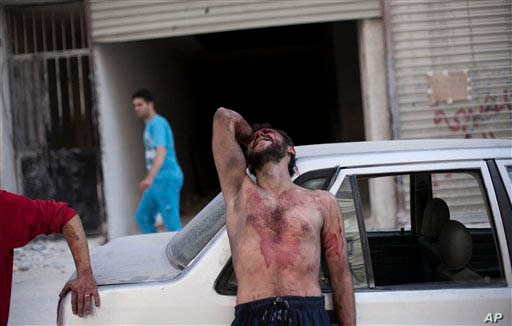 A Syrian man cries outside the Dar El Shifa hospital in Aleppo, Syria after his daughter was injured during a Syrian Air Force strike over a school where hundreds of refugees had taken shelter Thursday, Oct. 4, 2012.