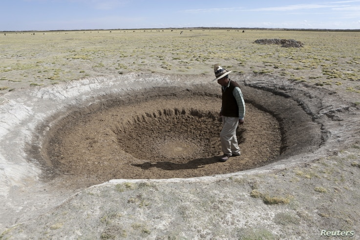 FILE - Farmer Sindulfo Fernandez inspects a dried watering hole for llamas in Orinoca, Oruro Department, Bolivia, Jan. 8, 2016. The water dried due to a drought.