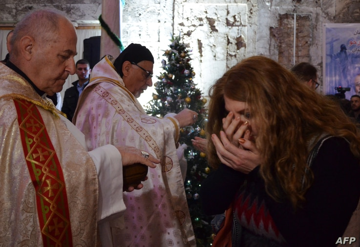 An Iraqi receives the Eucharist during a Christmas mass at the Saint Paul's church on Dec. 24, 2017 in the country's second city Mosul.