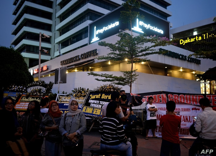 """A """"Pray for Jakarta"""" message (top) is displayed on a screen as Indonesians gather outside the damaged Starbucks coffee shop in central Jakarta on Jan. 17, 2016 following the deadly gun and bomb attacks that rocked the city on Jan. 14."""
