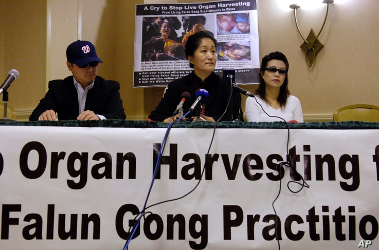 FILE - Dr. Wenyi Wang (C) holds a press conference with others, who preferred not to be identified, in Arlington, Virginia, April 26, 2006, about her having interrupted Chinese President Hu during his speech at the White House during his visit to Was...