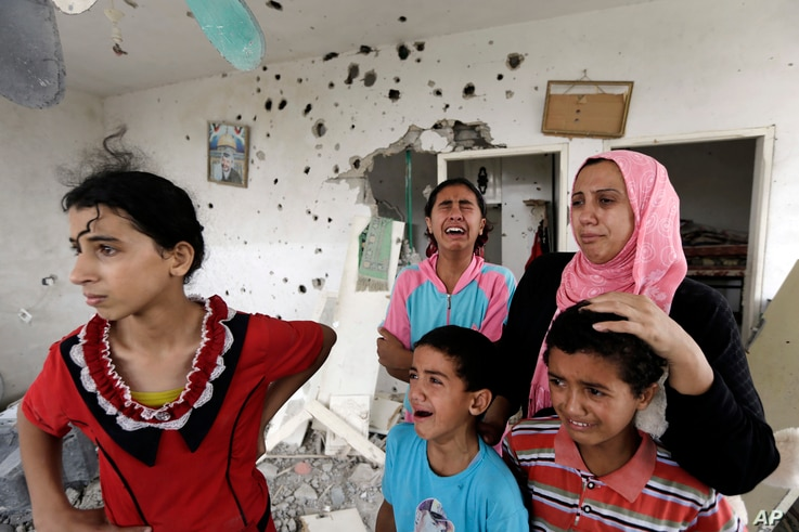 Palestinian Salwa Shabat, right, accompanied by some of her children, from left to right, Amira, Huda, top, Ahmed and Anas, weep as they inspect the damage upon returning to the family house, destroyed by Israeli strikes in the town of Beit Hanoun, n...