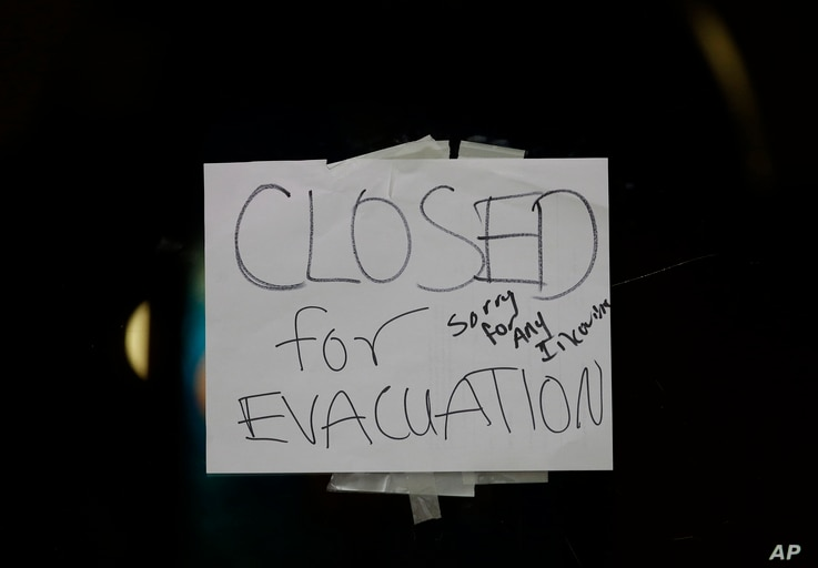 A closed sign is displayed on the door of Papaciito's restaurant due to an evacuation order, Feb. 12, 2017, in Marysville, Calif.