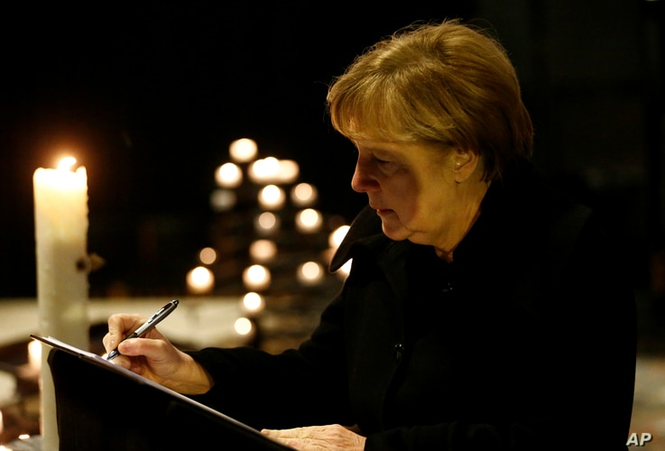 German Chancellor Angela Merkel signs the condolence book at the Memorial Church in Berlin, Germany, Tuesday Dec. 20, 2016, one day after a truck ran into a crowded Christmas market in Berlin and killed several people.
