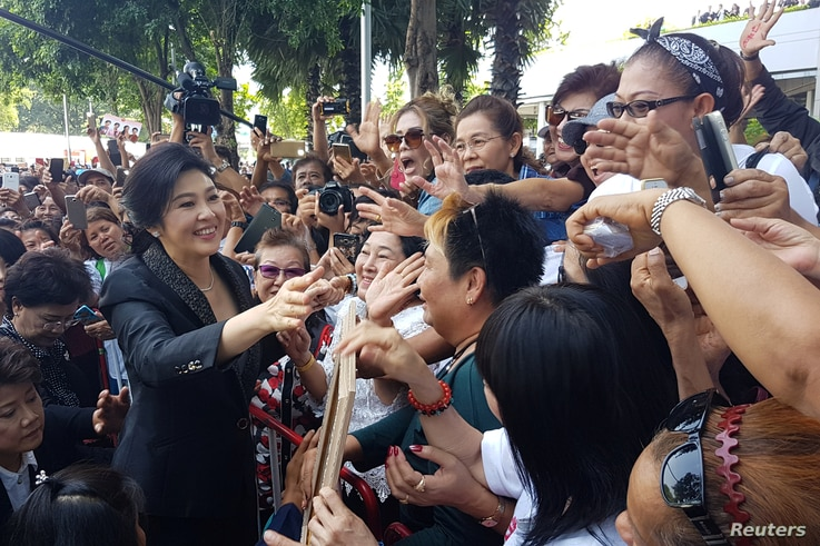 Ousted former Thai Prime Minister Yingluck Shinawatra greets supporters as she leaves the Supreme Court in Bangkok, Thailand, Aug. 1, 2017.