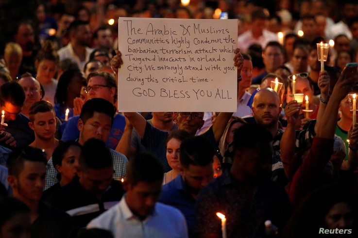 A man holds up a sign saying Arab Muslims condemn the attack as he takes part in a candlelight memorial service after a mass shooting at the Pulse gay nightclub in Orlando, Florida, June 13, 2016.