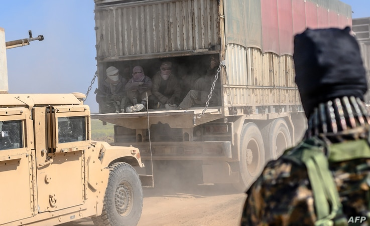 A truck carries men identified as Islamic State group fighters who surrendered to Kurdish-led Syrian Democratic Forces (SDF) as they are transported out of IS's last holdout of Baghuz, Syria, Feb. 20, 2019.