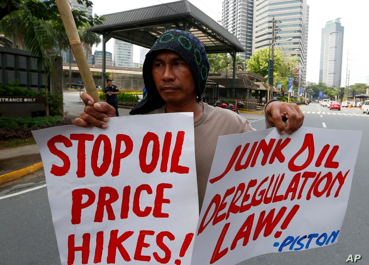 Protesters, mostly public transport drivers, display placards as they picket Petron Oil, the country's largest oil company, to protest the almost-weekly price increase of oil and other products and to demand its total rollback, June 5, 2018 in suburb...