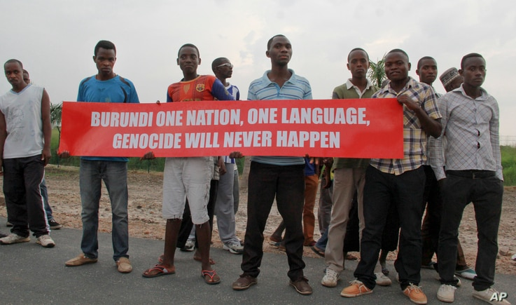 Young men hold a banner on the road that the convoy of the United Nations Security Council delegation took, in Bujumbura, Burundi, Jan. 21, 2016.