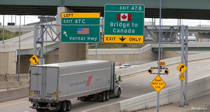 FILE - A commmercial truck exits the highway for the Ambassador Bridge to Canada, in Detroit, Michigan, Aug. 30, 2018.