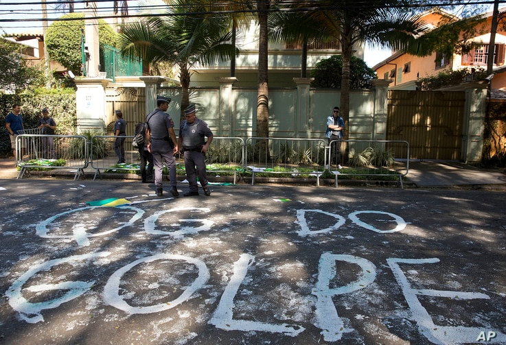 """Police stand guard outside the residence of Brazil's Vice President Michel Temer where demonstrators wrote the words in Portuguese """"Coup headquarters"""" on the street in Sao Paulo, Brazil, April 21, 2016, days after the lower house of Congress voted to..."""