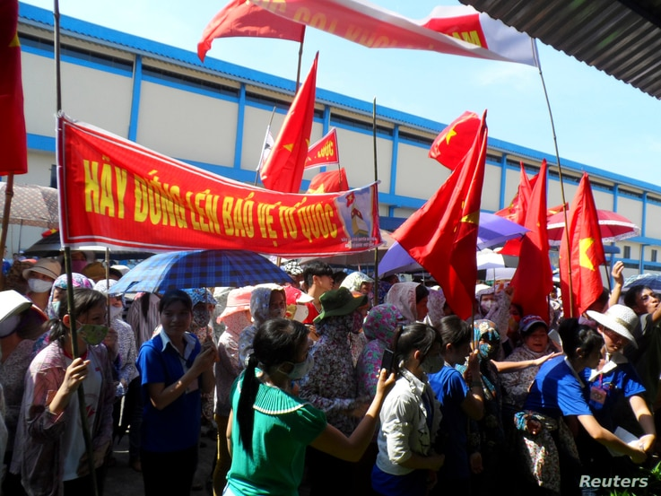 FILE - Workers wave Vietnamese national flags during an anti-China protest at a Chinese shoe factory in Vietnam's northern Thai Binh province, May 14, 2014. Thousands of Vietnamese set fire to foreign factories and rampaged in industrial zones in the...