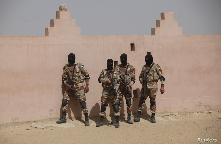 FILE - Pakistan Rangers stand before taking their positions during a counterterrorism training demonstration on the outskirts of Karachi, Feb. 24, 2015.