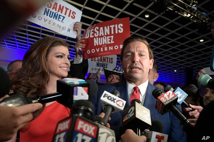 Florida Governor-elect Ron DeSantis, right, answers questions from reporters, with his wife Casey, after being declared the winner of the Florida gubernatorial race at an election party in Orlando, Fla., Nov. 6, 2018.