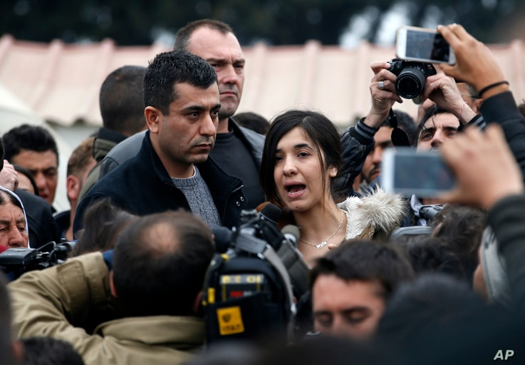FILE - Former Islamic State captive Iraqi Yazidi Nadia Murad, center, speaks during a visit in a makeshift refugee camp at the northern Greek border point of Idomeni, Greece, April 3, 2016.