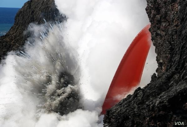 An open lava stream continues to pour out of the lava tube, perched high on the sea cliff, and into the ocean. The stream was remarkably steady today, but produced pulsating littoral explosions that threw spatter onto the sea cliff.