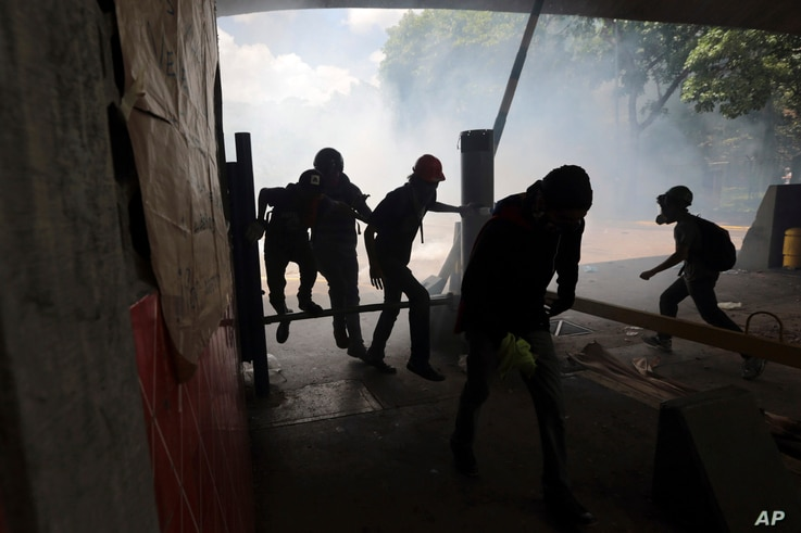Students run from tear gas fired by National Police outside the Central University of Venezuela in Caracas, May 4, 2017.