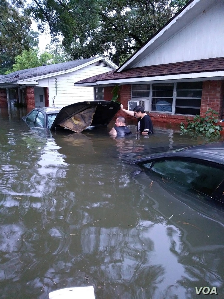 Andrew Saldivar, left, removes a car battery given to him by a neighbor, which he later installed on a boat to save Houstonians still stranded by the floods. (Photo courtesy of Andrew Saldivar)
