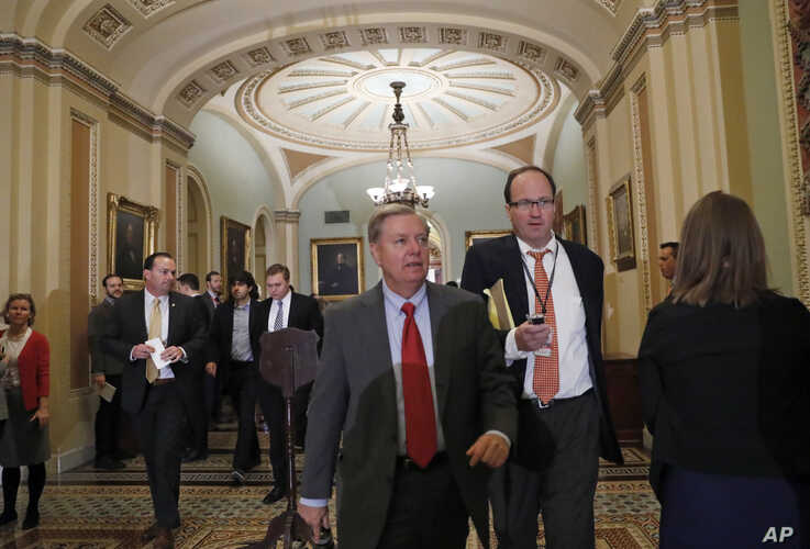 FILE - Senator Lindsey Graham walks with a reporter on Capitol Hill in Washington.