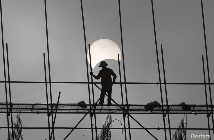FILE - A partial solar eclipse is seen as a labourer works at a construction site in Phnom Penh, Cambodia.