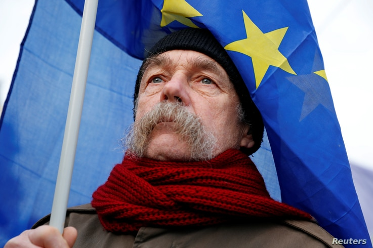 "A man holds an EU flag as he takes part in a protest against a proposed new labor law, billed as the ""slave law"", in Budapest, Hungary, Jan. 19, 2019."