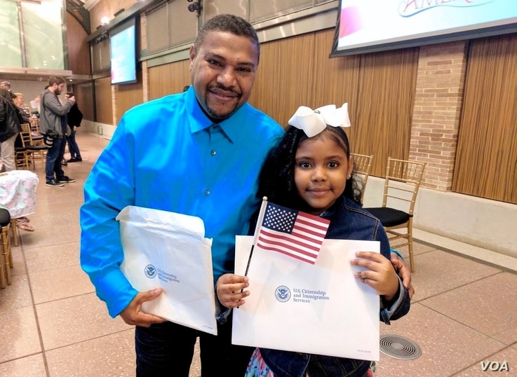 Dominican-American Luz Estrella Luna, 8, shows off her certificate of U.S. citizenship alongside her dad, Luis, after a citizenship ceremony in New York, May 5, 2017.  (R. Taylor/VOA)