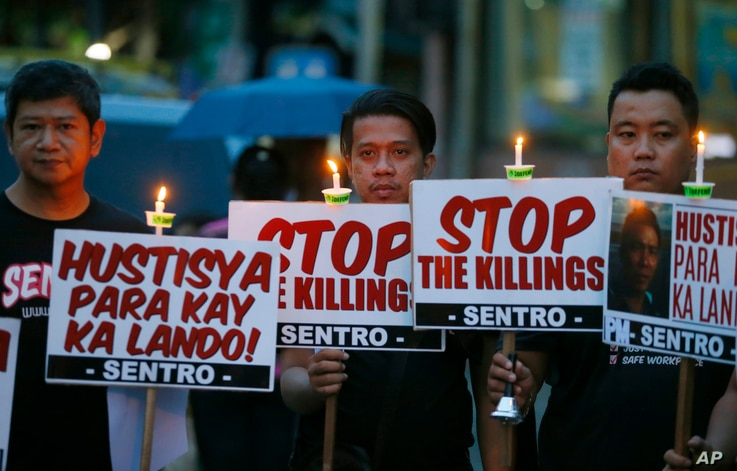 """Protesters hold placards in a candlelit protest against extrajudicial killings in President Rodrigo Duterte's """"War on Drugs"""" campaign in suburban Quezon city, northeast of Manila, Philippines, Oct. 8, 2016."""