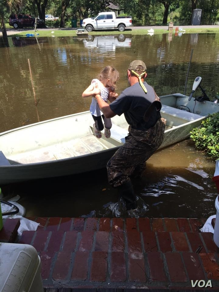 Graham Kinchen of St. Amant, Louisiana, takes time off to give his daughter a boat ride — in their front yard. (D. Kinchen./VOA)