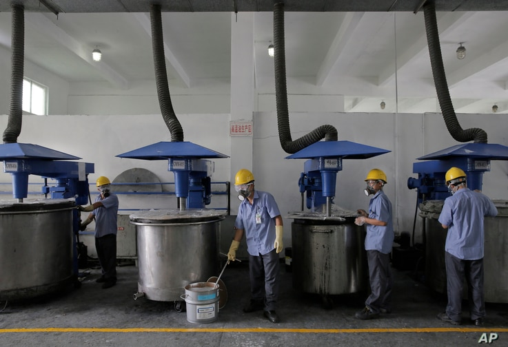 Workers in masks and safety helmets inspect mixing machines at GMM non-stick coatings factory in Zhuhai, Guangdong province, China, May 6, 2015.