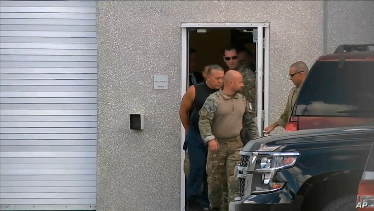This frame grab from video provided by WPLG-TV shows FBI agents escorting Cesar Sayoc, in sleeveless shirt, in Miramar, Florida, on Oct. 26, 2018. Sayoc was identified by authorities as the Florida man who send pipe bombs to some President Trump's mo...