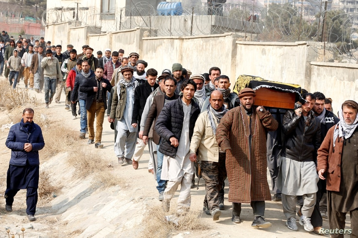 Afghan men carry the coffin of one of the victims of the attack on Kabul, Afghanistan, Jan. 28, 2018. On Saturday, a car bomb ripped through a crowded area outside a government building. Hundreds were killed or wounded.